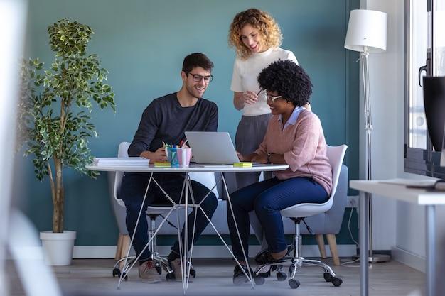 Foto de empresários jovens casuais trabalhando com laptop e falando sobre o novo projeto juntos no escritório.