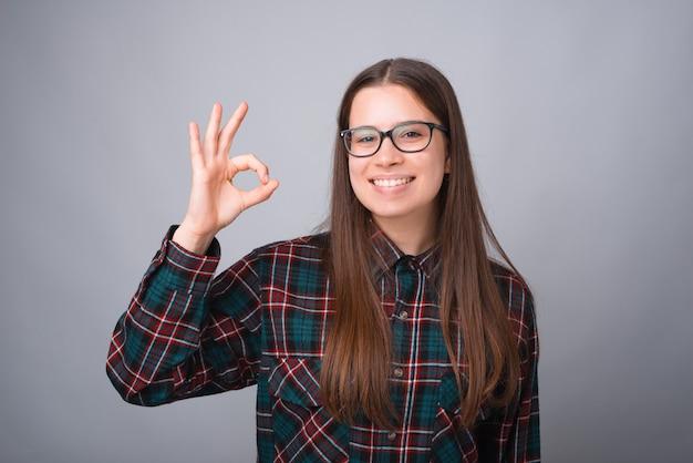 Foto de encantadora jovem sorridente, mostrando o gesto ok
