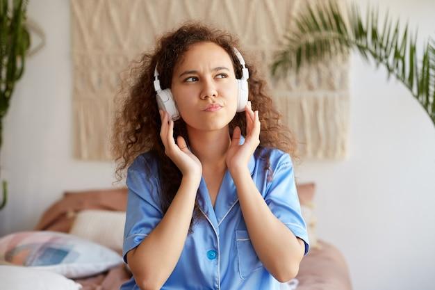 Foto de encaracolado jovem simpática senhora afro-americana, ouvindo música favorita em fones de ouvido, segura os fones de ouvido, pensativamente desvia o olhar.