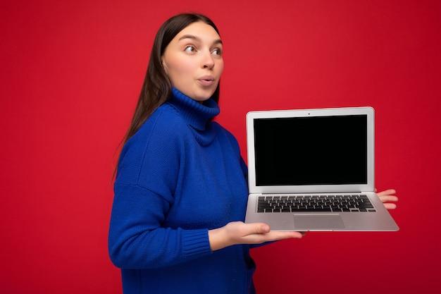 Foto de espantado e surpreso jovem morena segurando o laptop do computador, olhando para o lado, vestindo uma blusa azul isolada sobre o fundo da parede vermelha. mock up, cutout