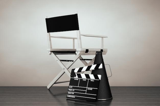 Foto de estilo antigo. cadeira do diretor, movie clapper e megafone no chão