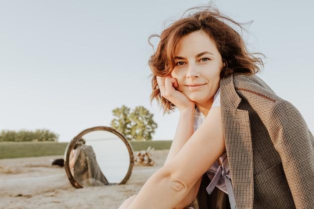 Foto de estilo de vida atmosférica ao ar livre da bela jovem de cabelos escuros em jaquetas, sentado na praia e espelho de reflexão.