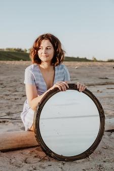 Foto de estilo de vida atmosférica ao ar livre da bela jovem de cabelos escuros no vestido azul, sentado na praia e segurando o espelho.