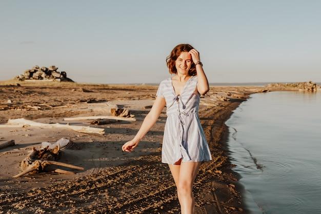Foto de estilo de vida atmosférica ao ar livre de jovem morena bonita com vestido de verão, caminhando na praia.