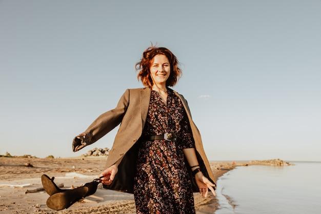 Foto de estilo de vida atmosférica ao ar livre de jovem morena bonita de vestido e jaqueta caminhando na praia.