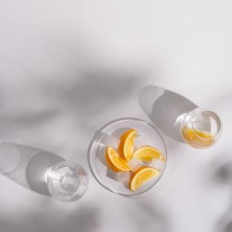 Foto de estilo de vida com copos de vidro com água fria e uma fatia de laranja no prato branco