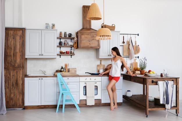 Foto de estilo de vida da linda garota de pé junto ao fogão na cozinha, cozinhando e cheirando bons aromas de fritura de alimentos