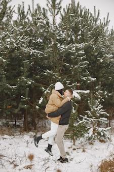 Foto de estilo de vida de casal caminhando em um bosque nevado