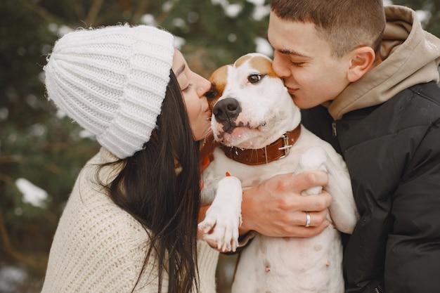 Foto de estilo de vida de casal em um bosque nevado com cachorro