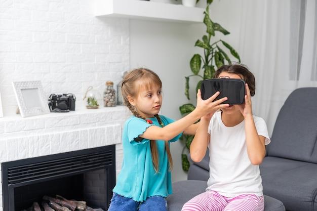 Foto de estilo de vida de duas crianças espantadas usando óculos de realidade virtual na sala de estar de casa.