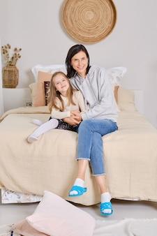 Foto de estilo de vida de mãe e filha sentadas na cama em casa