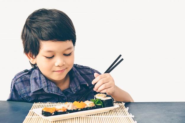 Foto de estilo vintage de asiático adorável menino está comendo sushi