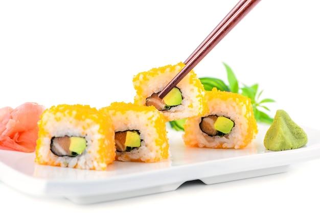 Foto de estoque de makis em um prato com pauzinhos apresentados com gengibre e wasabi
