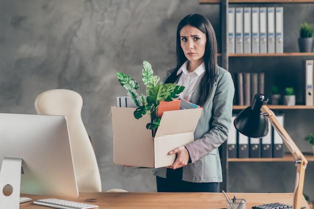 Foto de estressada frustrada deprimida garota ceo comerciante perder emprego empresa falida precisa pesquisar mercado segurar caixa de papelão usar jaqueta blazer na estação de trabalho