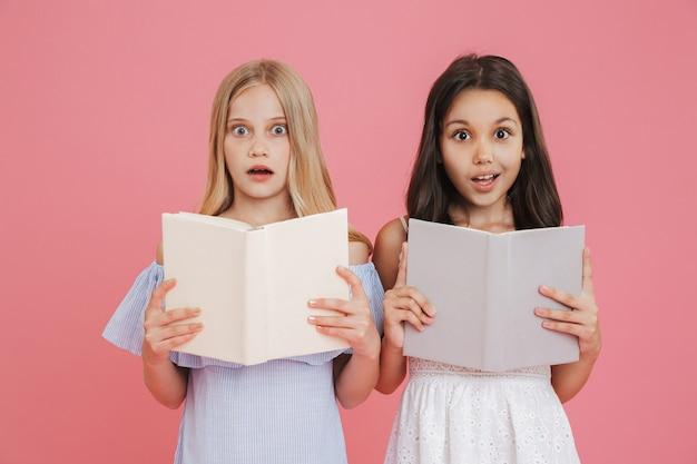Foto de estudante morena e loira usando vestidos segurando e lendo livros junto com a empolgação, isolada sobre fundo rosa