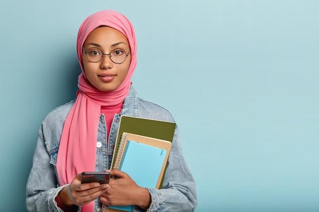 Foto de estudante muçulmano carrega bloco de anotações, segura celular moderno, cria nova publicação nas redes sociais, cobre a cabeça com véu segundo regras religiosas, conversa com colegas de grupo online