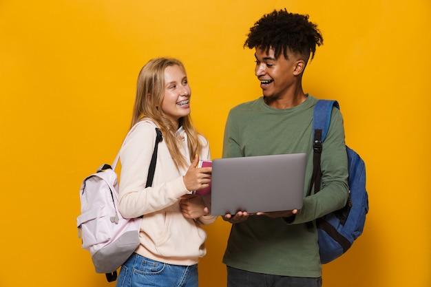Foto de estudantes adolescentes, homem e mulher, de 16 a 18 anos, usando mochilas, segurando um laptop prateado e cadernos de exercícios, isoladas sobre fundo amarelo