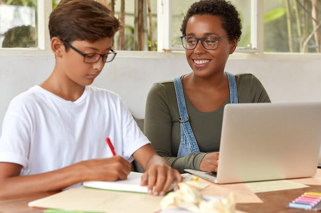 Foto de estudantes adolescentes multiétnicos envolvidos no processo de trabalho, navegar pelas informações em um laptop portátil, escrever ideias para o trabalho do projeto no bloco de notas, sentar na mesa, verificar a mensagem de renda