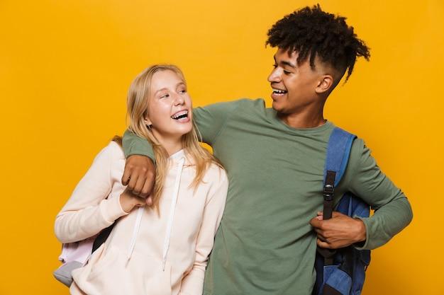 Foto de estudantes alegres, homem e mulher de 16 a 18 anos, usando mochilas, rindo e se abraçando, isolado sobre um fundo amarelo
