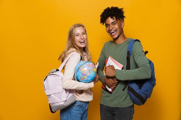 Foto de estudantes americanos e caucasianos, homem e mulher de 16 a 18 anos, usando mochilas segurando um globo terrestre, isolado sobre o fundo amarelo