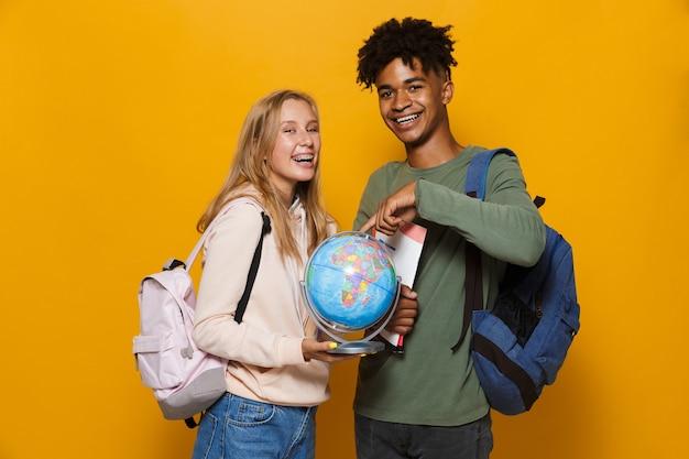Foto de estudantes felizes, homem e mulher de 16 a 18 anos, usando mochilas segurando um globo terrestre e cadernos de exercícios, isolados sobre um fundo amarelo