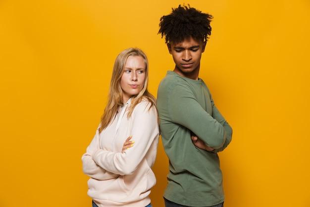 Foto de estudantes infelizes, homem e mulher de 16 a 18 anos, em pé, costas com costas, numa briga, isolada sobre fundo amarelo