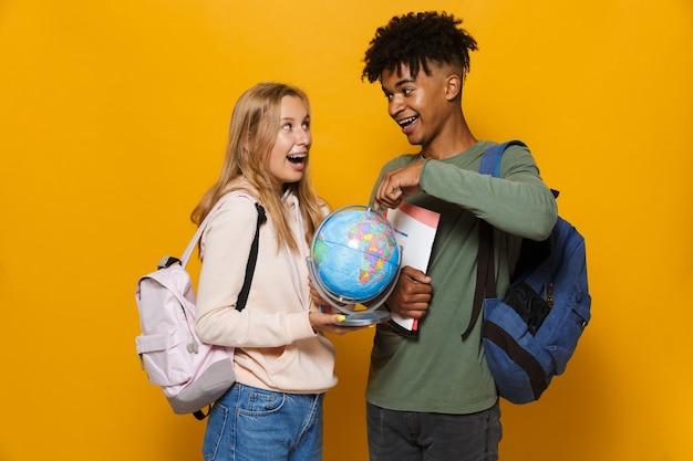 Foto de estudantes inteligentes, homem e mulher de 16 a 18 anos, usando mochilas segurando um globo terrestre e cadernos, isolados sobre um fundo amarelo