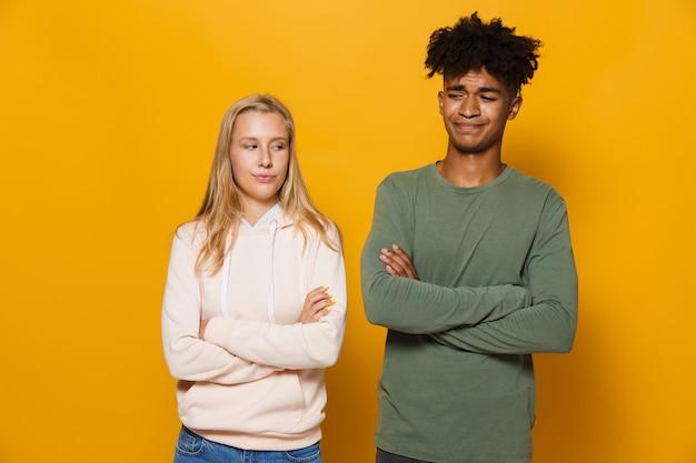 Foto de estudantes irritados, homem e mulher de 16 a 18 anos, com os braços cruzados após uma discussão, isolado sobre um fundo amarelo