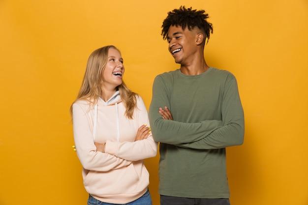 Foto de estudantes multiétnicos, homem e mulher, de 16 a 18 anos com aparelho dentário rindo, isolada sobre fundo amarelo