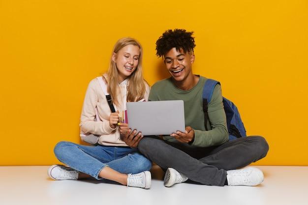 Foto de estudantes multiétnicos, homem e mulher, de 16 a 18 anos, usando um laptop prateado, sentado no chão, com as pernas cruzadas, isolado sobre um fundo amarelo