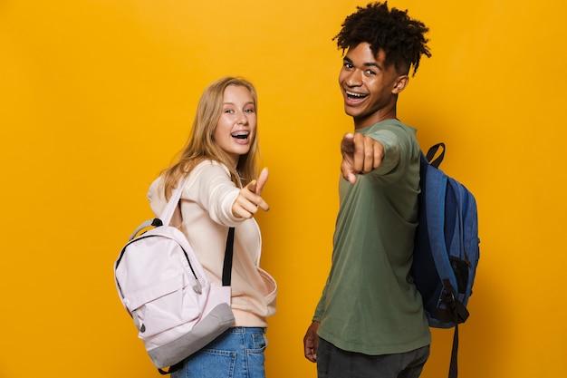 Foto de estudantes rindo, homem e mulher, de 16 a 18 anos, usando mochilas, apontando o dedo para você, isolada sobre fundo amarelo
