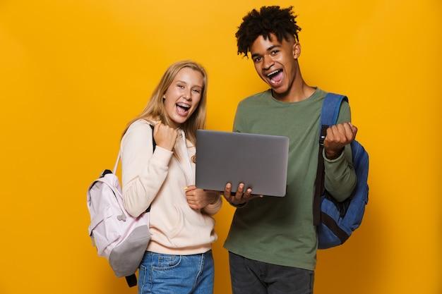 Foto de estudantes satisfeitos, homem e mulher de 16 a 18 anos, usando mochilas, segurando um laptop prateado e cadernos de exercícios, isolados sobre um fundo amarelo