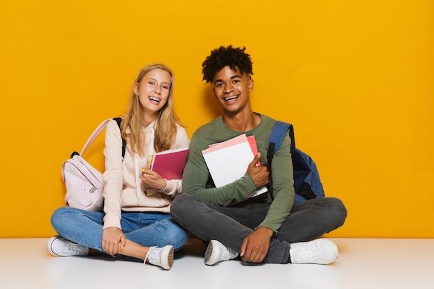 Foto de estudantes sorridentes, homem e mulher de 16 a 18 anos, segurando cadernos de exercícios enquanto está sentado no chão com as pernas cruzadas, isolado sobre um fundo amarelo