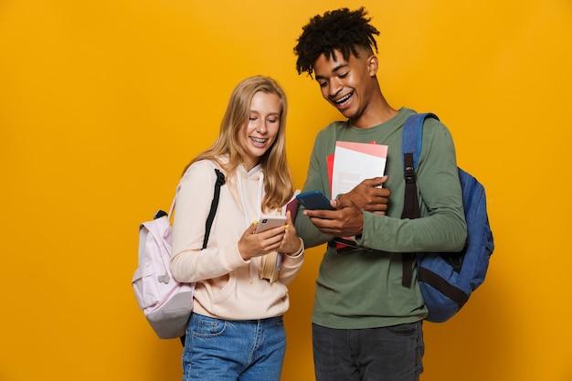 Foto de estudantes universitários, homem e mulher de 16 a 18 anos, usando mochilas, sorrindo enquanto seguram cadernos e um telefone celular, isolado sobre um fundo amarelo