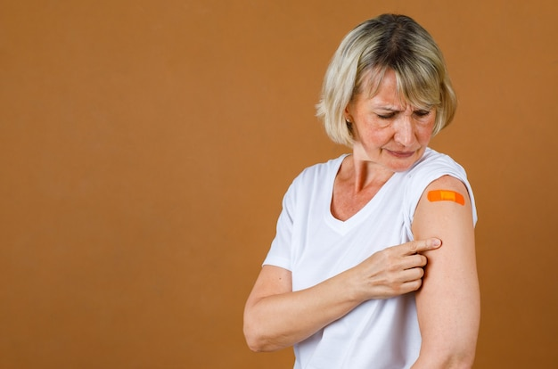Foto de estúdio closeup retrato de paciente caucasiano sênior loira ficar estressando tem dor olhar para ferida de injeção em bandagem de gesso laranja em seu ombro após receber a vacinação de covid-19.