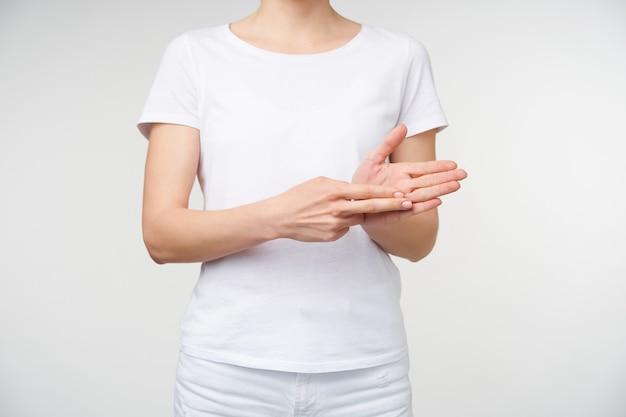 Foto de estúdio com as mãos levantadas de uma jovem sendo levantadas enquanto mostra o trem de palavras usando a linguagem de pessoas surdas, isolado sobre um fundo branco em roupas casuais