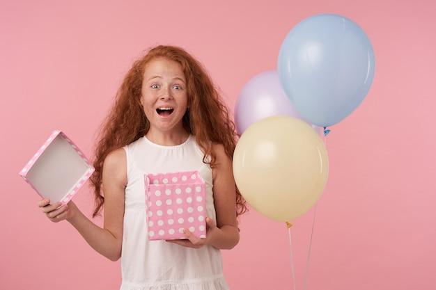 Foto de estúdio da adorável ruiva segurando uma caixa embrulhada para presente com uma cara animada, olhando alegremente para a câmera com as sobrancelhas levantadas, em pé sobre um fundo rosa com balões coloridos