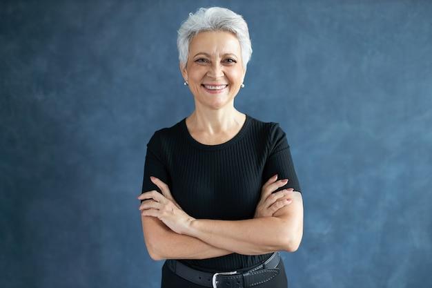Foto de estúdio da bela feliz aposentada caucasiana com penteado de duende cruzando os braços sobre o peito, com um olhar confiante e sorrindo amplamente