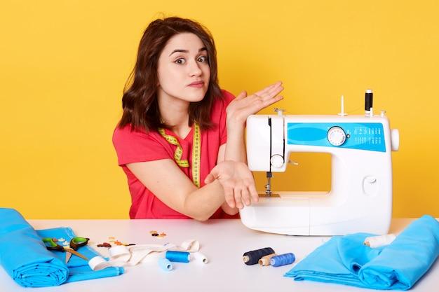 Foto de estúdio da costureira de menina sentada na mesa branca com máquina de costura