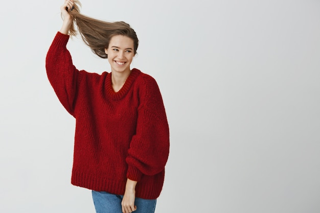 Foto de estúdio da fêmea europeia atraente despreocupada com sorriso sensual, levantando o cabelo saudável bonito com a mão, olhando de lado e expressando a atitude relaxada do concurso, em pé sobre a parede cinza