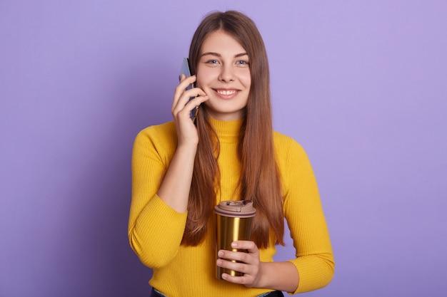 Foto de estúdio da garota sorridente muito feliz vestindo camisa casual amarela