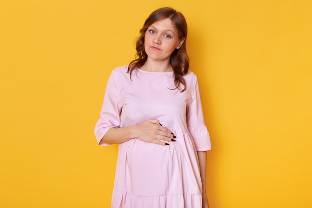Foto de estúdio da jovem mulher grávida bonita usando vestido rosa em pó e segurando a mão na barriga