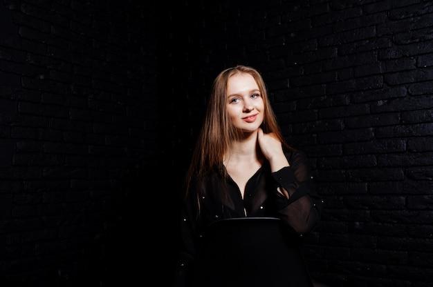 Foto de estúdio da menina morena de blusa preta com sutiã e shorts contra a parede de tijolo preta.