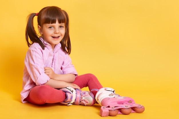 Foto de estúdio da menina sorridente feliz sentada no chão