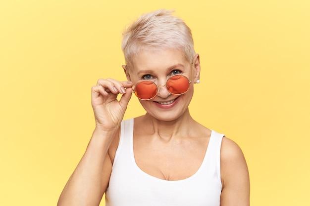 Foto de estúdio da moda glamourosa mulher de meia idade com corte de cabelo de duende posando isolada tirando seus elegantes óculos de sol redondos.