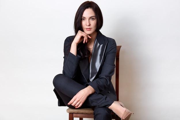 Foto de estúdio da mulher morena confiante, sentado na cadeira de madeira e mantendo o punho sob o queixo