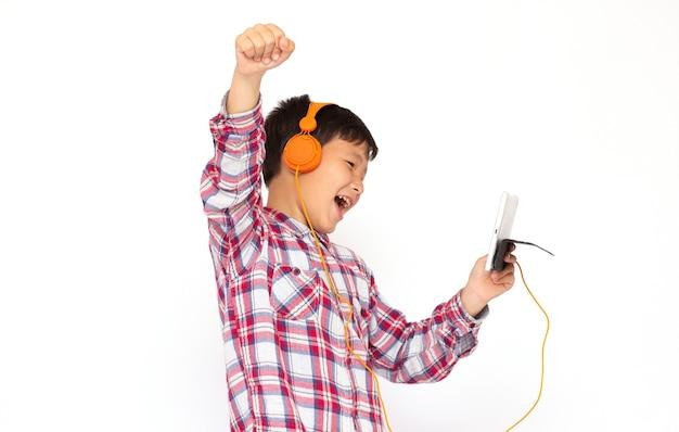 Foto de estúdio de adolescente ouvindo música em fones de ouvido e gritando enquanto olha para um tablet, isolado sobre a superfície branca