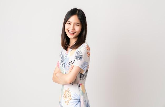 Foto de estúdio de alegre linda mulher asiática em vestido de cor clara e carrinho com os braços cruzados em fundo branco.