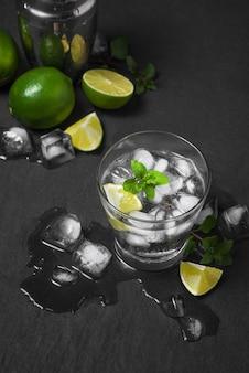 Foto de estúdio de bebidas frescas de mojito com fatias de limo, isoladas em um fundo de pedra cinza