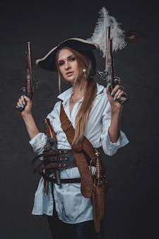Foto de estúdio de bucaneiro de mulher vestindo uma camisa branca e tricórnio segurando armas.